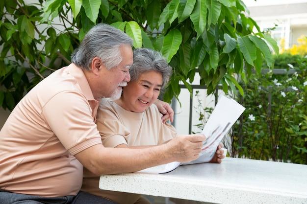 Asiatisches älteres paar, das lachend liest, während zeitung auf dem tisch draußen im vorgartenhaus liest