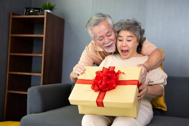 Asiatisches älteres paar mit geschenkbox zu hause, jubiläums- oder weihnachtsfeiertagskonzept.