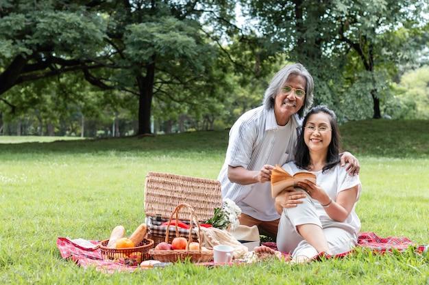 Asiatisches älteres paarlesebuch und -picknick am park.