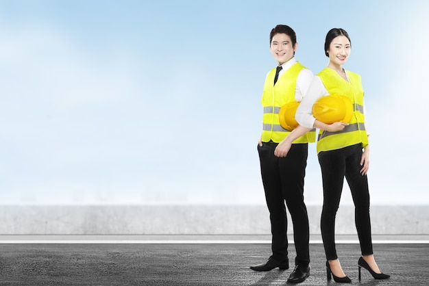 Asiatisches arbeiterteam, das einen gelben helm stehend hält