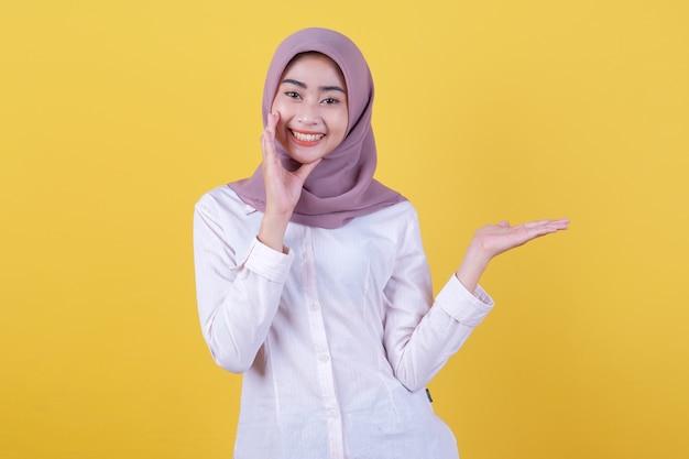 Asiatisches attraktives mädchen zeigt etwas zur hand und flüsterte etwas mit hijab