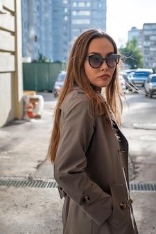 Asiatisches attraktives modell, das trenchcoat und sonnenbrille trägt, die nahe wand bei sonnigem wetter stehen