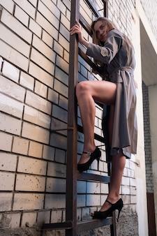 Asiatisches attraktives modell mit trenchcoat, das auf der feuerleiter an der wand steht standing