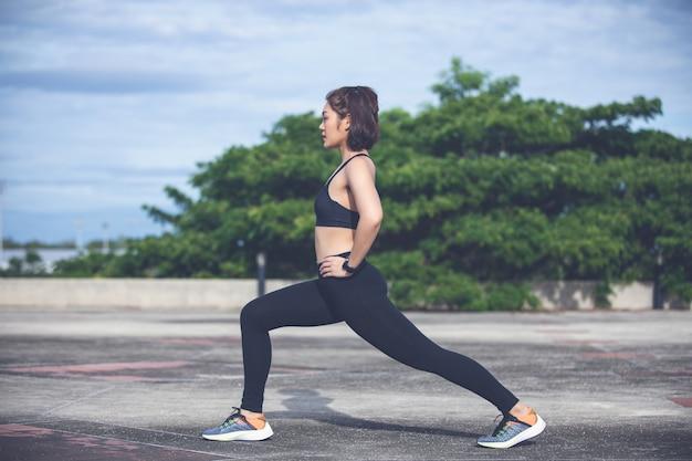 Asiatisches aufwärmen der athletischen frau und junger weiblicher athlet, die auf einem trainieren und ausdehnen in einen park vor läufer draußen, gesunder lebensstil sitzt