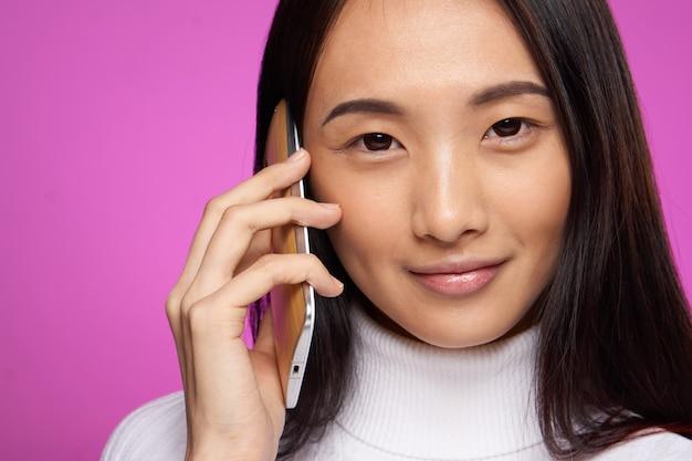 Asiatisches aussehen der frau, die auf dem rosa lächeln des telefon-nahaufnahme-studios spricht.
