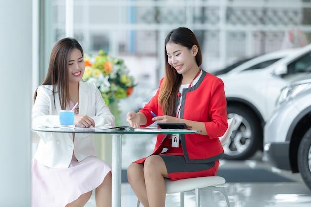 Asiatisches autogeschäft, autoverkauf, technologie und leutekonzept - glückliches paar mit auto.