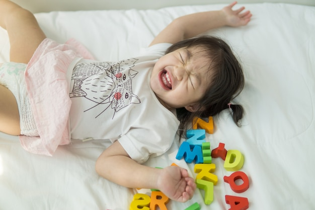 Asiatisches baby, das abc-buchstaben auf einem bett spielt