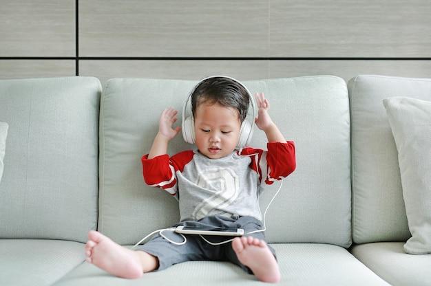 Asiatisches baby, das auf sofa sitzt und musik durch kopfhörer hört