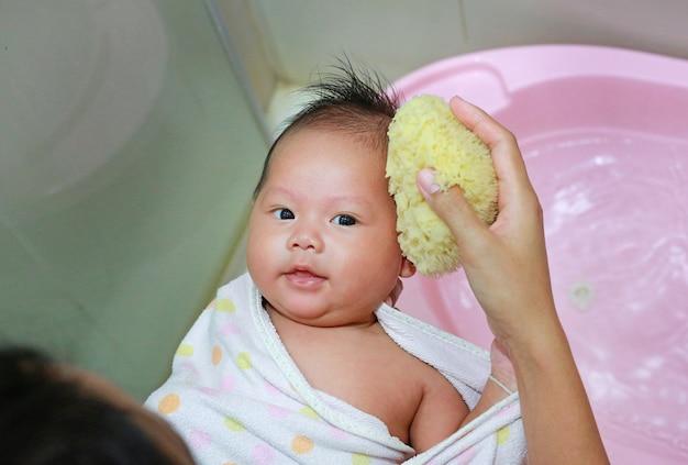 Asiatisches baby, das ein bad mit schwamm hat
