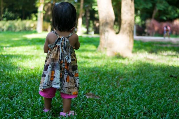 Asiatisches baby, das im garten spielt