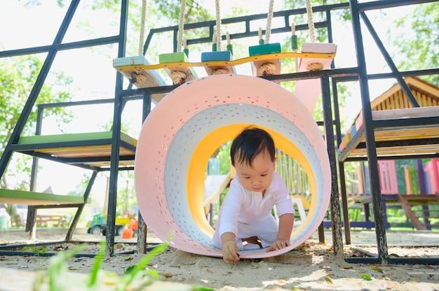 Asiatisches baby, das mit sand in einem sandkasten spielt. gesundes aktives baby im freien spielt spielzeug