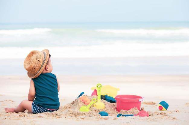 Asiatisches baby, das sand auf dem strand, baby einjährig spielt