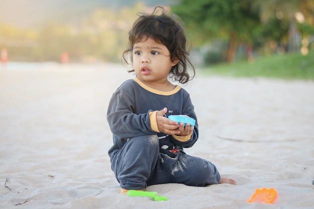 Asiatisches baby, das strandspielzeug auf dem sandstrand nahe dem meer spielt