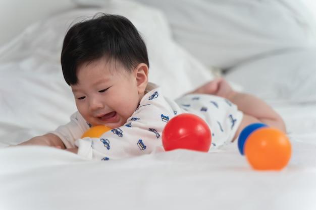 Asiatisches baby lacht und spielt spielzeugball auf weißem bett mit dem gefühl glücklich und nett und dem baby, das auf das bett kriecht.