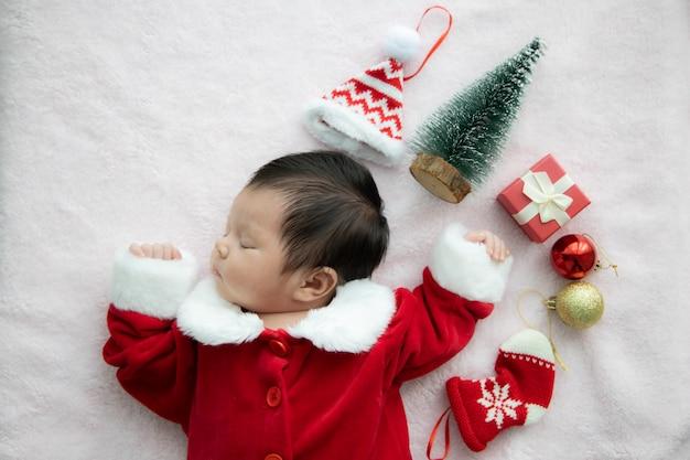 Asiatisches baby neugeboren auf weihnachtsmann-uniform schlafend mit rotem kastengeschenk und rotem hut