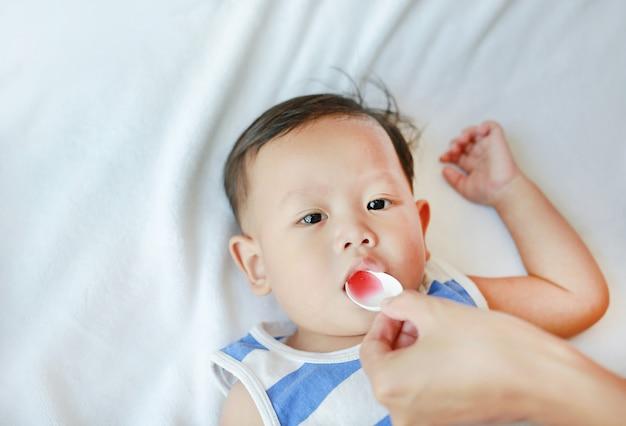 Asiatisches baby nimmt medizinsirup von einem löffel. krankes kind.