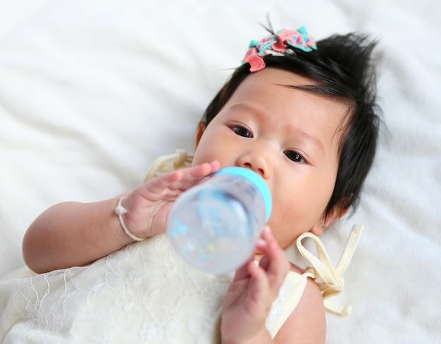 Asiatisches babykind, das milch von der flasche durch selbst isst.
