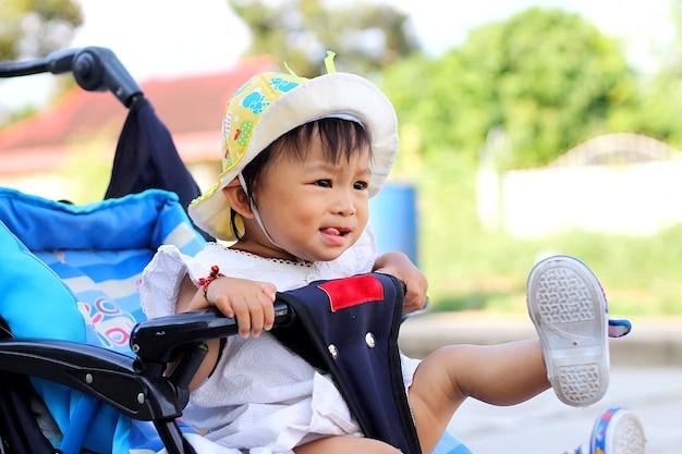 Asiatisches babykindermädchen, das in einem spaziergänger sitzt. verspieltes kind.