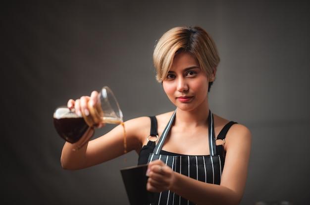 Asiatisches barista-mädchen, das kaffee macht, frisches kaffee, das filtertropfenwerkzeug gießt