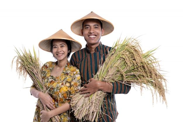 Asiatisches bauernpaar, das reiskörner hält