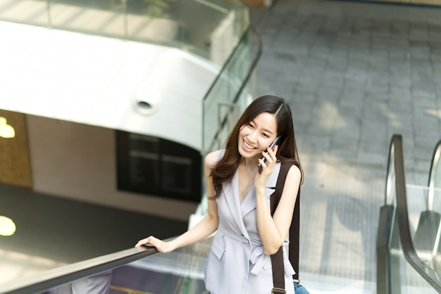 Asiatisches büromädchen, das am handy steht auf aufzug im einkaufszentrum spricht.