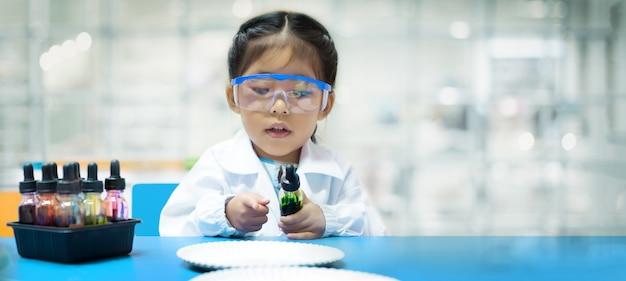 Asiatisches chemisches kind experimentiert mit bildungsfähigkeiten