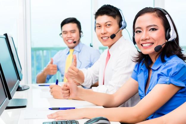 Asiatisches chinesisches kundenkontaktcenter-agententeam am telefon