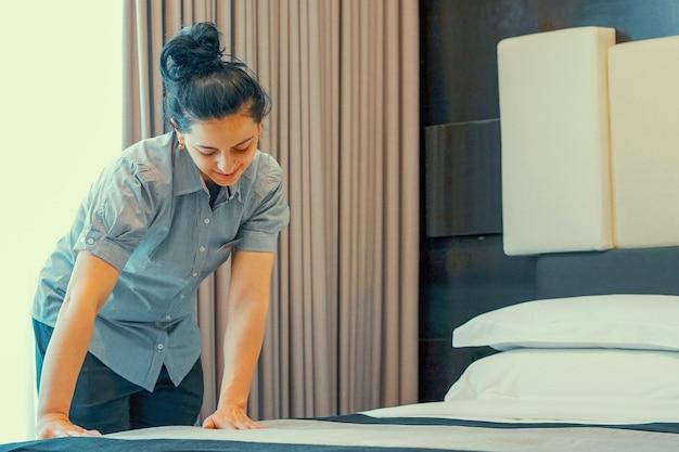 Asiatisches dienstmädchen macht bett im hotelzimmer