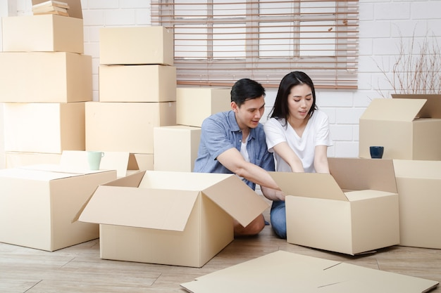 Asiatisches ehepaar zieht in ein neues zuhause ein packen sie die braune papierschachtel aus, um das haus zu dekorieren. konzept, ein neues leben zu beginnen, eine familie zu gründen. speicherplatz kopieren