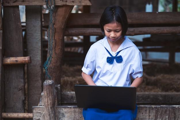 Asiatisches einheitliches studentenmädchen, das computernotizbuch verwendet