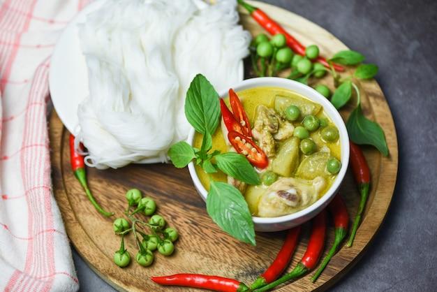Asiatisches essen auf dem tisch. grünes curry-huhn des thailändischen essens auf suppenschüssel und thailändischen reisnudeln fadennudeln mit zutat kräutergemüse