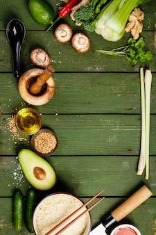 Asiatisches essen auf grünem tischhintergrund, draufsicht
