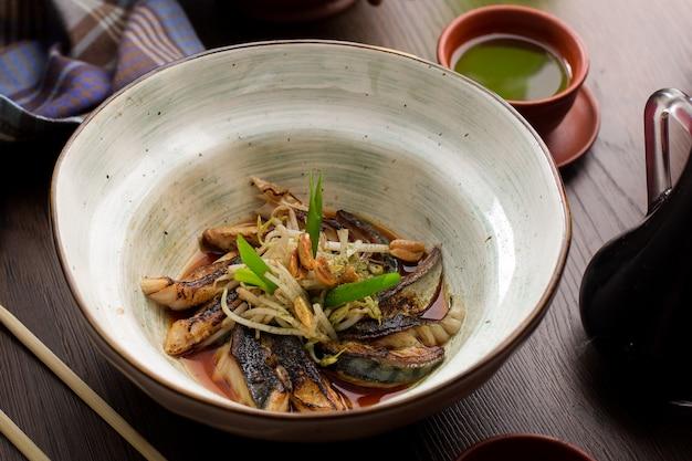 Asiatisches essen: fisch mit sprossen und erdnüssen in einem restaurant