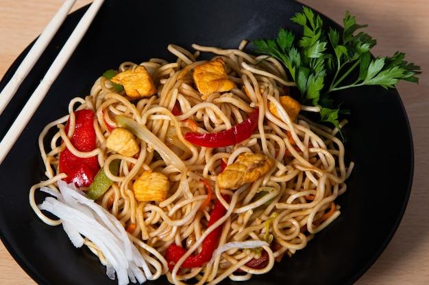 Asiatisches essen, gebratene yakisoba-nudeln mit hühnchen. isoliertes bild.