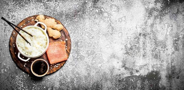 Asiatisches essen. gekochter reis mit einem stück lachs und sojasauce. auf rustikalem hintergrund. tisch mit japanischer küche.