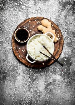 Asiatisches essen. gekochter reis mit sojasauce auf dem alten brett. auf rustikalem hintergrund. tisch mit japanischer küche.