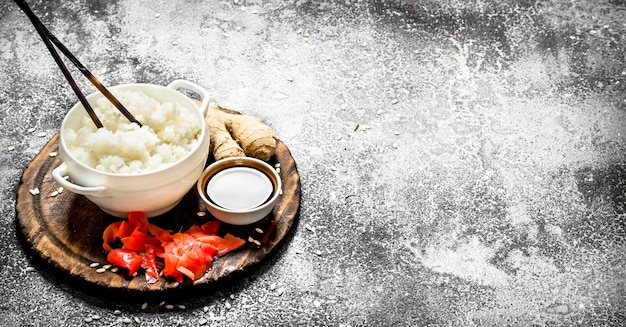 Asiatisches essen. gekochter reis mit sojasauce und eingelegtem ingwer. auf einem alten rustikalen hintergrund. tisch mit japanischer küche.