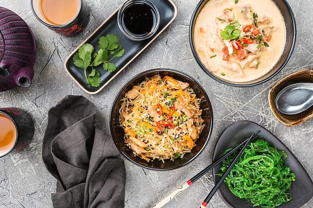 Asiatisches essen, gerichte der thailändischen küche. tom kha gai suppe, pad thai nudeln, grüner salat, saucen und grüner tee. draufsicht