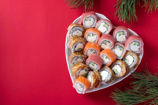 Asiatisches essen mit sushi-set aus lachs, thunfisch und aal mit philadelphia-käse auf teller in form eines herzens gegen eine rote oberfläche