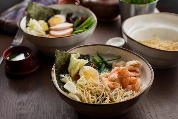 Asiatisches essen: ramen mit huhn und garnelen auf dem tisch