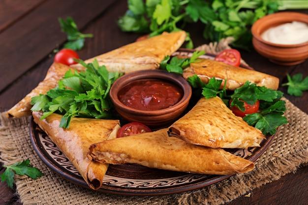 Asiatisches essen. samsa (samosas) mit hähnchenfilet und käse auf holz.