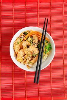 Asiatisches essen. teekanne und tasse, würzige shrimp poke bowl mit reis, algen und sesam, avocado auf rotem bambus mattenhintergrund mit stäbchen über dem roten bambushintergrund.