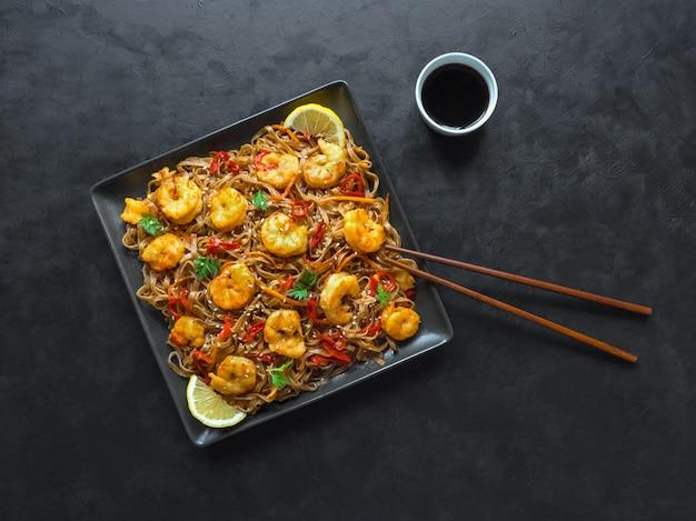 Asiatisches essen udon nudeln mit gebratenen garnelen, sesam und pfeffer nahaufnahme auf einem teller