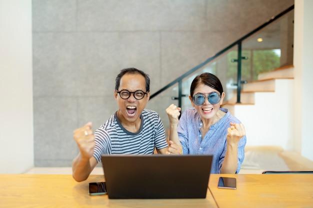 Asiatisches familienglücksgesicht, das auf laptop-computer schaut