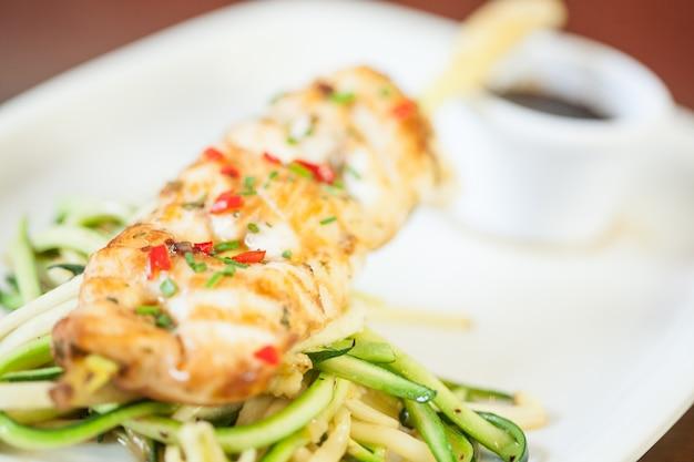 Asiatisches fischgericht mit nudeln und julienne-gemüse