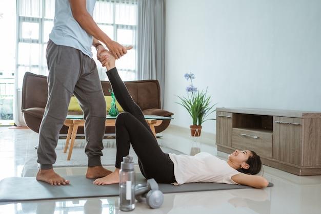 Asiatisches fitnesspaar, mann und frau, die zusammen zu hause yoga im wohnzimmer tun