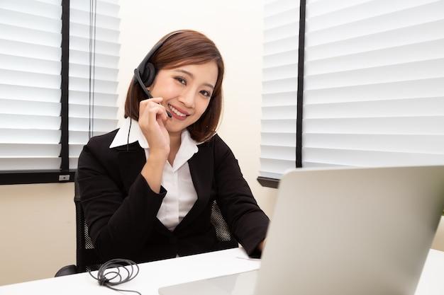 Asiatisches frauen-callcenter mit kopfhörer.