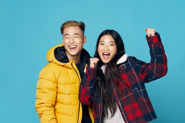 Asiatisches frauen- und mannpaar, das in der winterkleidung aufwirft