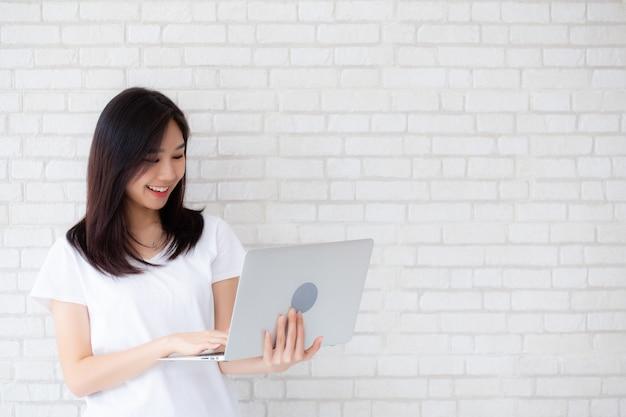 Asiatisches frauenlächeln des schönen porträts unter verwendung des laptops