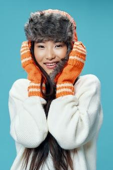 Asiatisches frauenmodell, das mit winterkleidung aufwirft